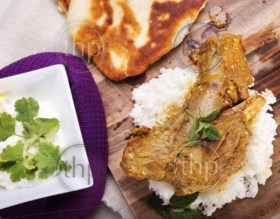 Slow cooked lamb shanks served on wooden board with rice and gluten free naan bread