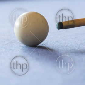 Pool Table - Microstock ManPool cue and the white ball in shallow focus on a pool table