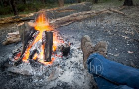 Person warms their feet next to a campfire at dusk camping in the woods