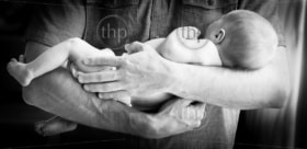 Cute newborn baby boy being held in his father's arms against his chest in black and white