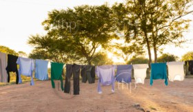 Mens and womens laundry drying on outdoor clothes line with pegs and sun streaming in behind