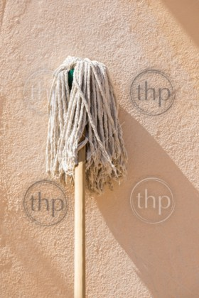 Classic wooden handled mop leaning up against a wall with room for text