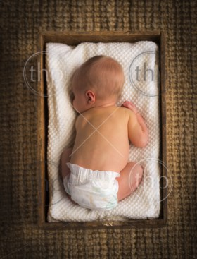 Newborn baby sleeping in a vintage wooden crate with white cloth