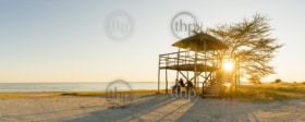 Group of friends sit relaxing at sunset on the beach under a large open air hut in Africa