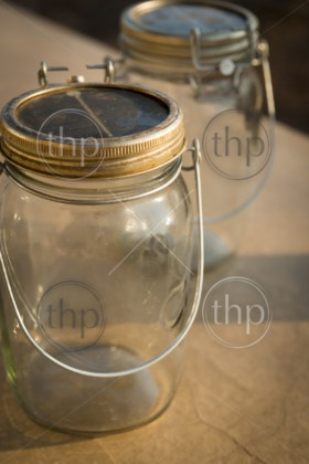 Mason jars with solar power panels powering an LED light under the lid in closeup