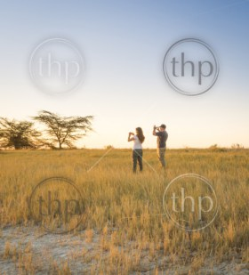 A young couple of tourists taking photos of an African sunset while on safari in the Makgadikgadi Pans, Botswana