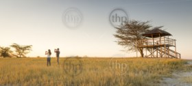 A young couple stand in long grass and watch the sunset while on safari in the Makgadikgadi Pans, Botswana, Africa