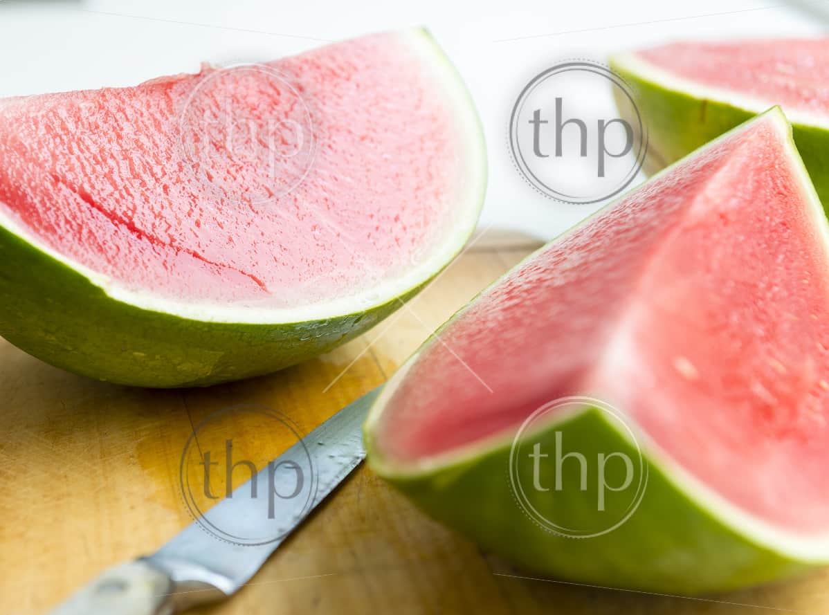 Fresh juicy watermelon sliced on wooden board in shallow focus