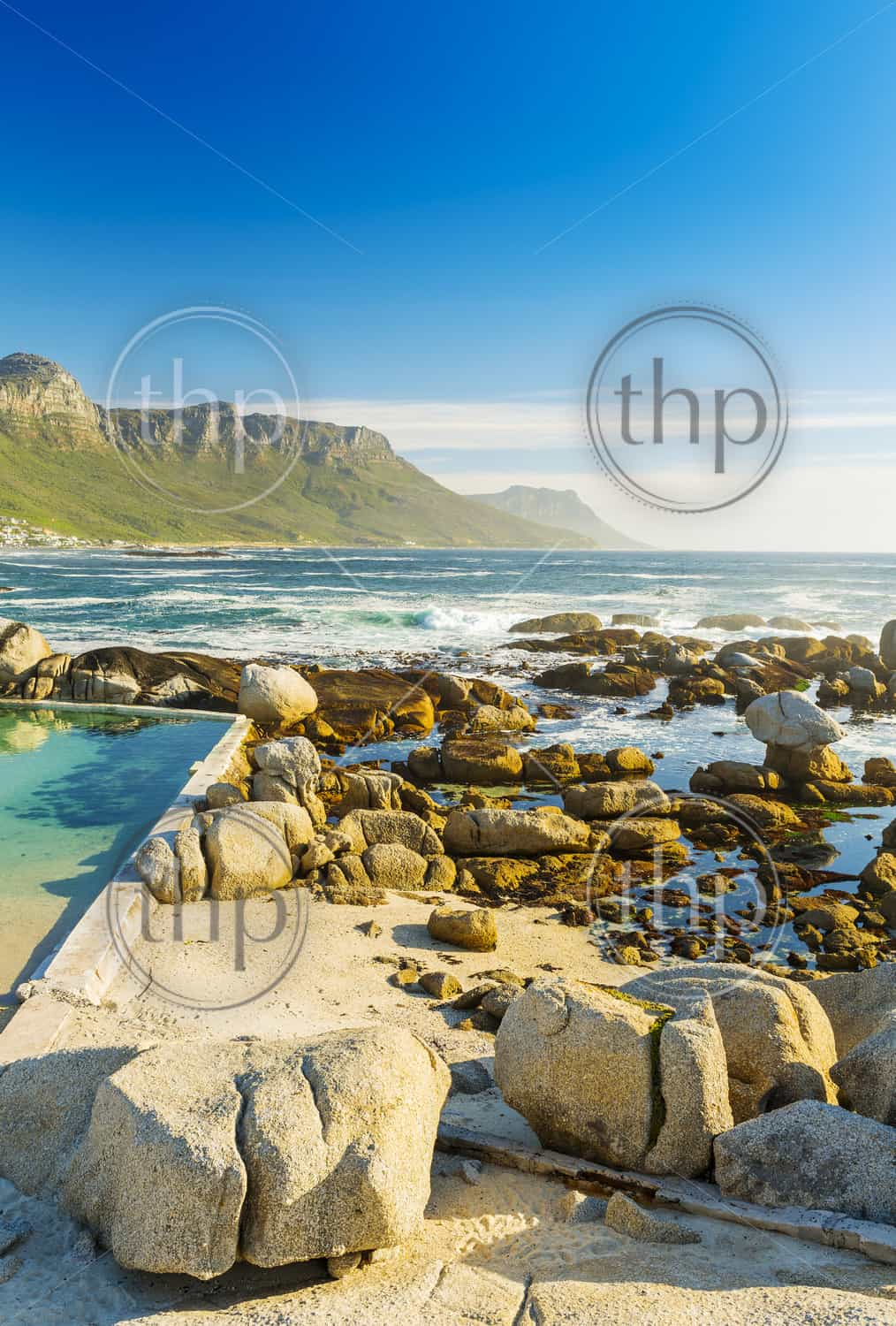 Camps Bay ocean rocks with Twelve Apostles behind