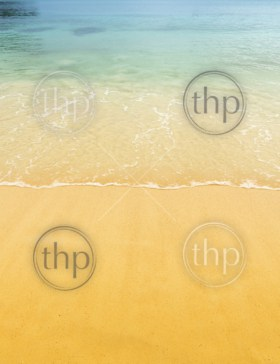 Beach background scene of tropical warm sand and clear water lapping the shore
