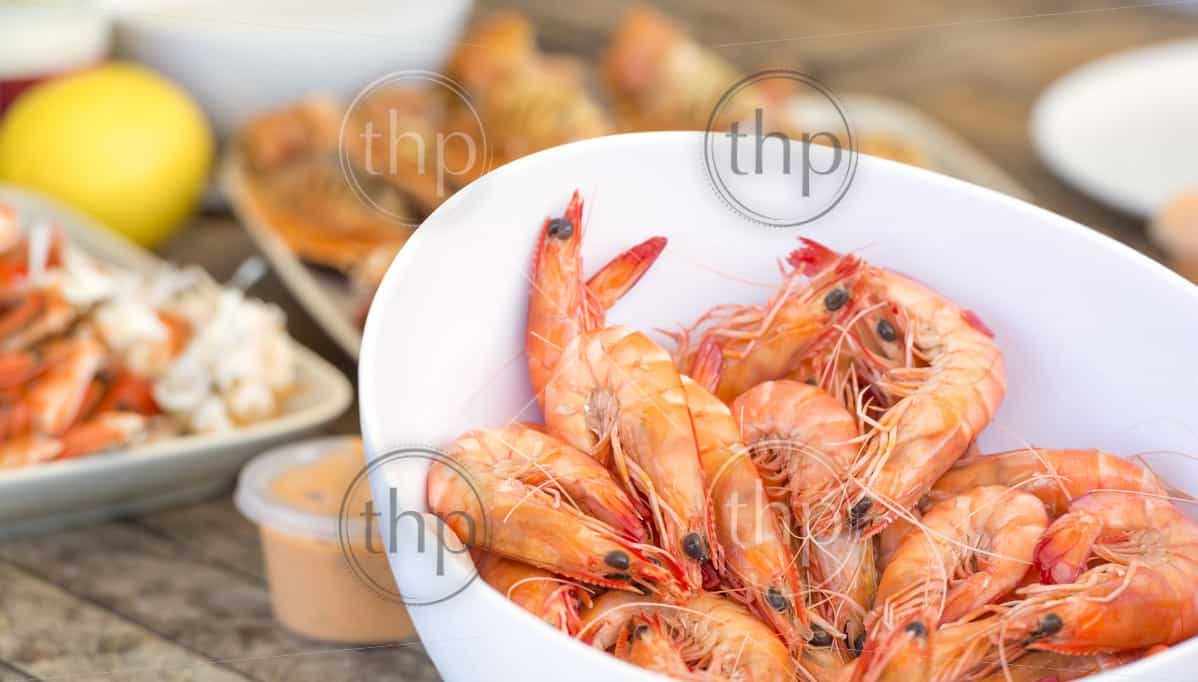 Bowl of large fresh prawns with other seafood behind