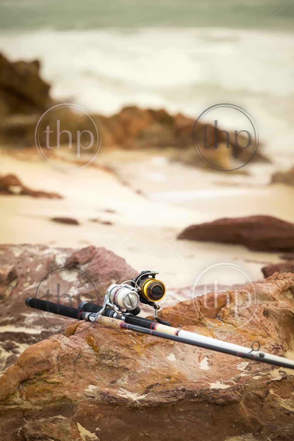 Fishing rods for surf fishing sitting on rocks at the beach