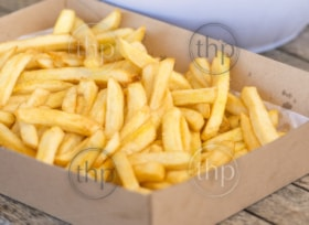 Serving of hot salty chips on a wooden table