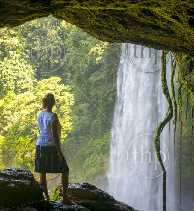 Tourist In cave looking out at Misol Ha Waterfall near Palenque in Chiapas, Mexico