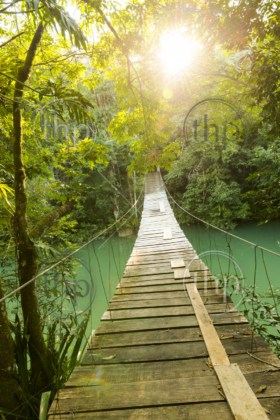 Epic wooden bridge hanging over jungle river as adventure travel scene