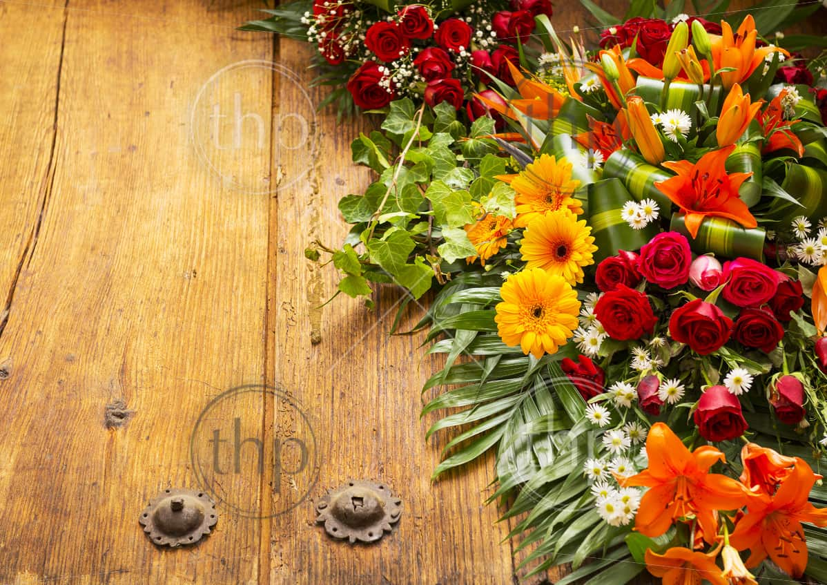 Floral wreath on weathered wooden door with copy space