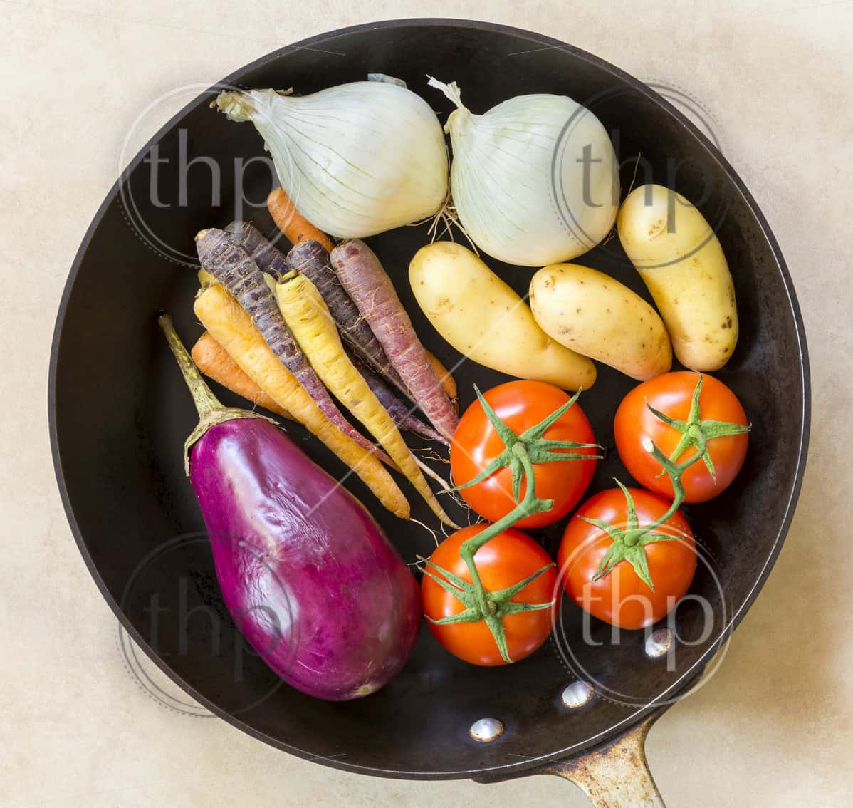 Fresh healthy vegetables ready for roasting in a deep black pan