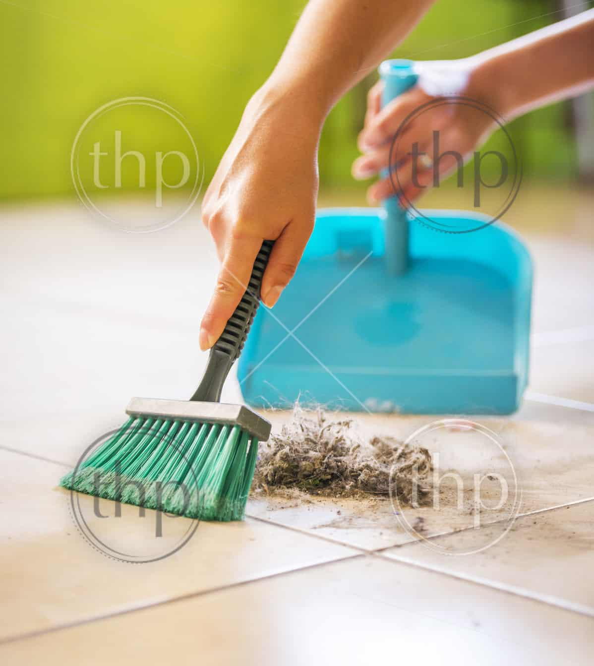 A woman sweeps up dust and dirt from the floor while cleaning the house